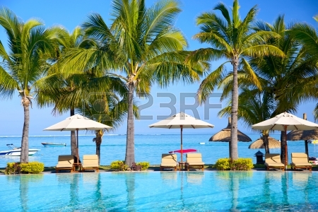 24813064-swimming-pool-with-lounge-chairs-and-umbrellas-on-beach-in-mauritius