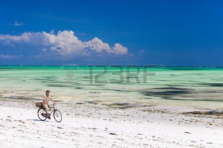 6436450-young-man-bicycling-along-tropical-beach-of-zanzibar-island